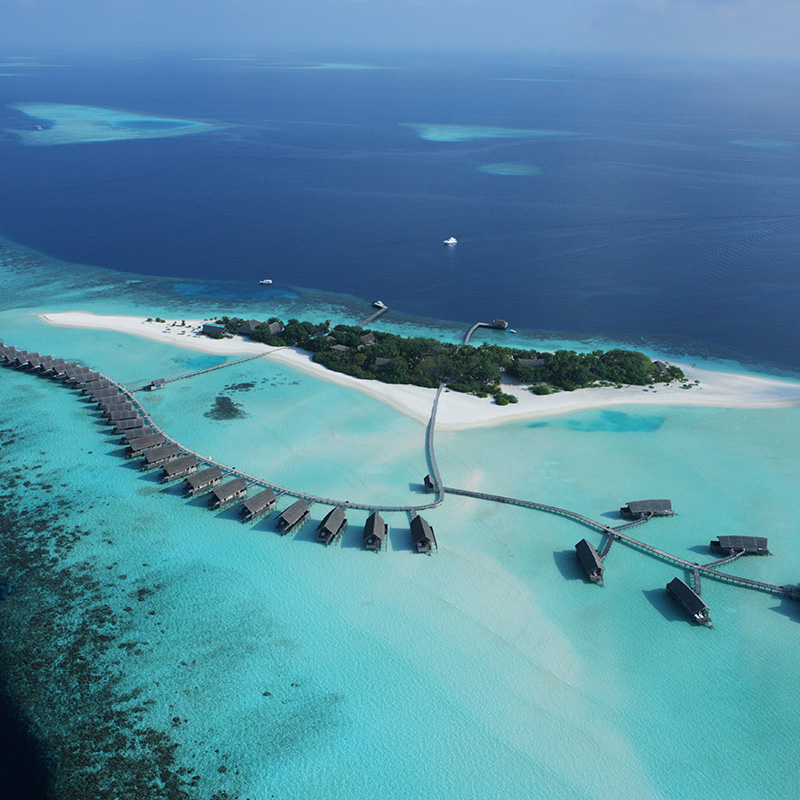 Aerial shot of island and bungalows on stilts in clear blue ocean