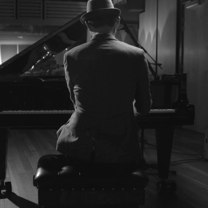Man in suit and hat playing grand piano