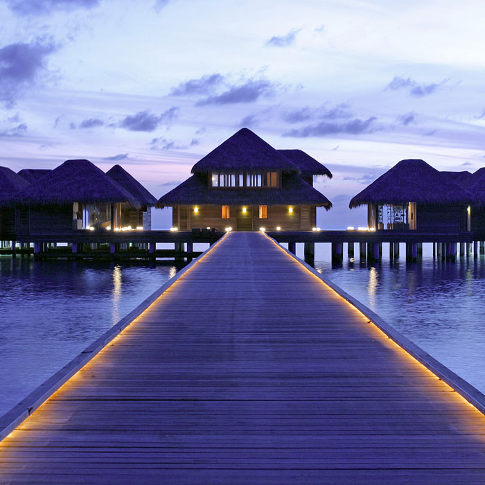 Maldives at night retreat spa walkway to bungalows built on water