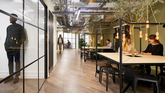 Industrial style office work space with trees and workers