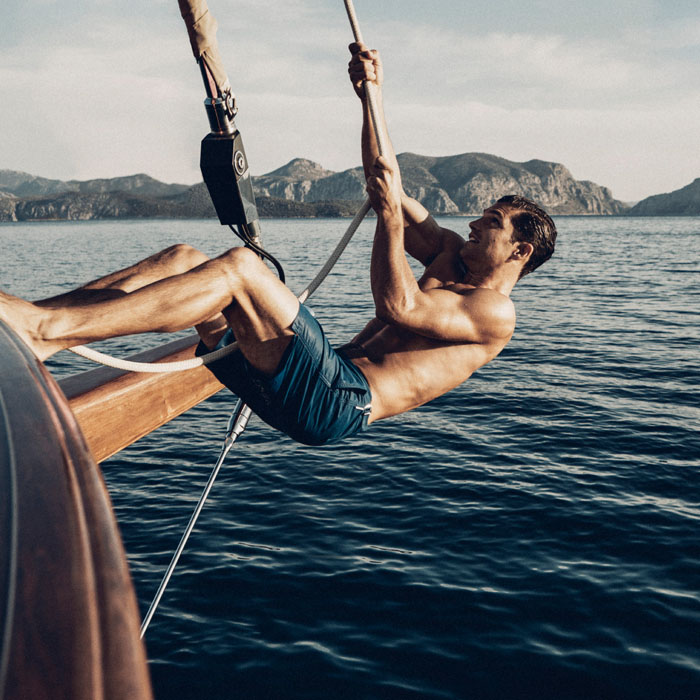 Man holding rope and leaning from side of boat in the sea in swimwear
