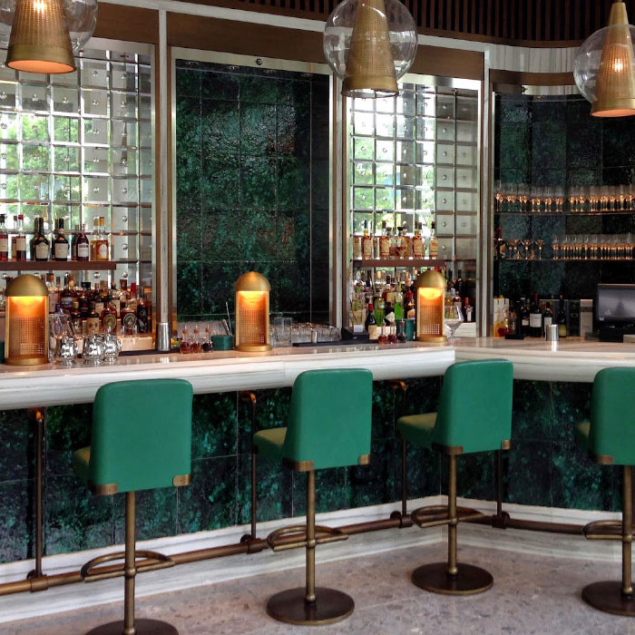 The Continental restaurant bar area with green swivel stools and cosmopolitan design
