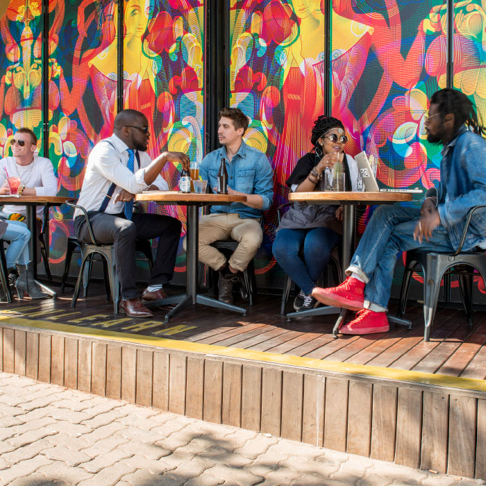 Multi-cultural diverse group of men and women enjoying drinks at a cafe in front of a colourful wall