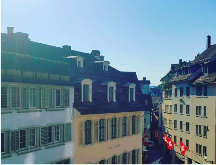 Buildings and rooftops in Zurich with Swiss flags