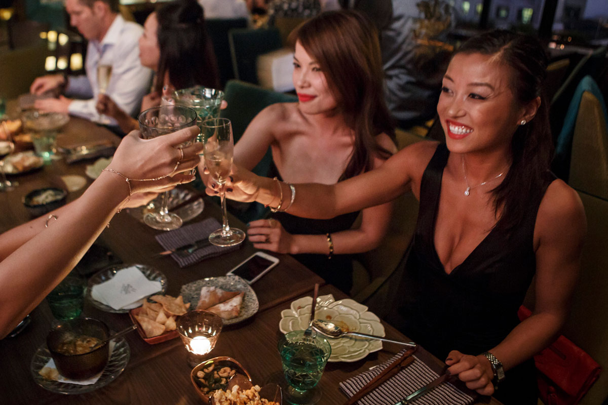 Women raising their glasses and enjoying a meal in a restaurant