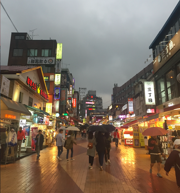 People walking along rainy street in Hongdae Seoul at night